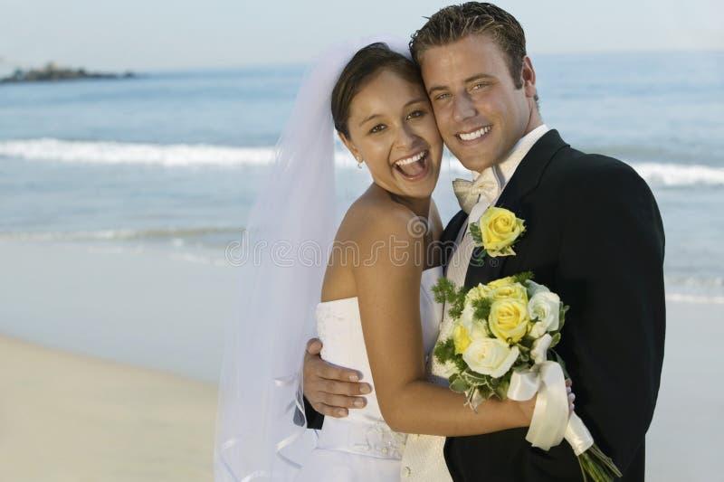 拥抱在海滩的新娘和新郎 免版税库存照片