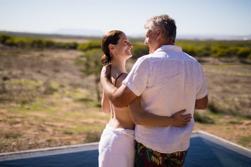 拥抱在游泳池边附近的微笑的夫妇 免版税图库摄影
