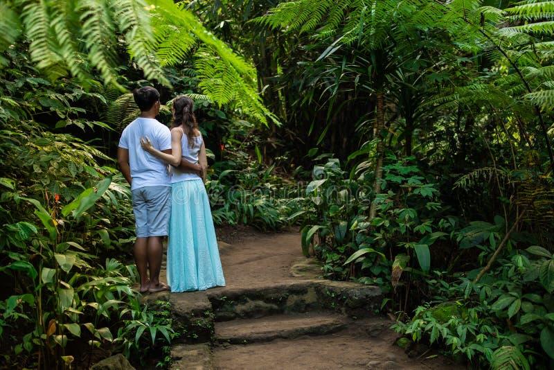 拥抱在热带森林年轻混合的族种夫妇的走的足迹的多种族夫妇在度假在亚洲 Ubud,巴厘岛,印度尼西亚 免版税库存图片
