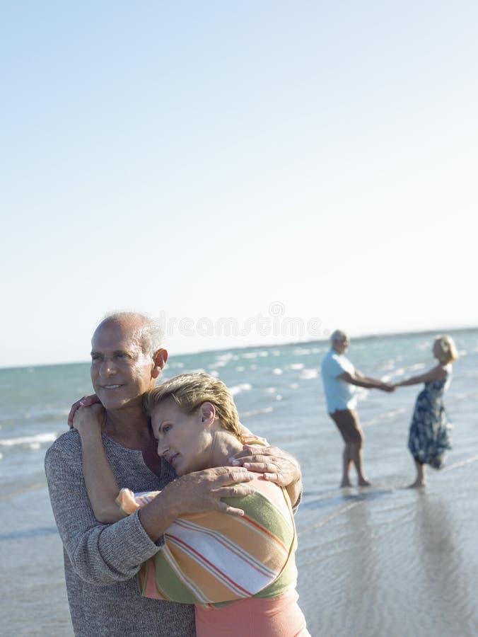 拥抱在热带海滩的资深夫妇 库存图片