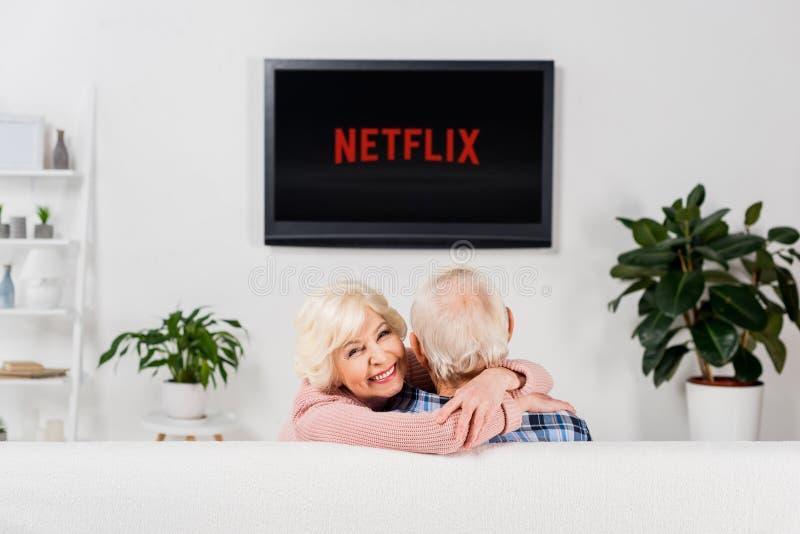 拥抱在电视前面的长沙发的资深夫妇与netflix商标 库存照片