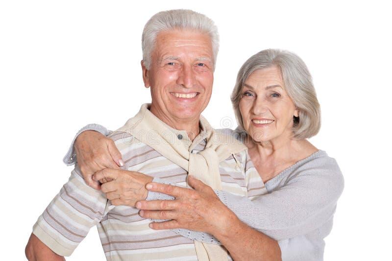 拥抱在白色背景的愉快的资深夫妇画象  免版税库存照片