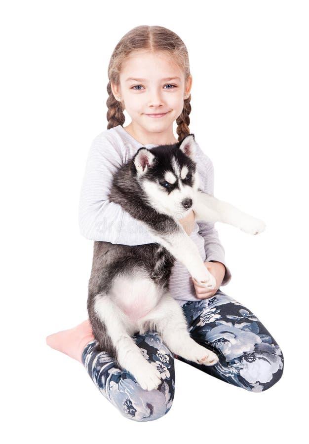 拥抱在白色背景的逗人喜爱的小女孩一只多壳的小狗 库存照片