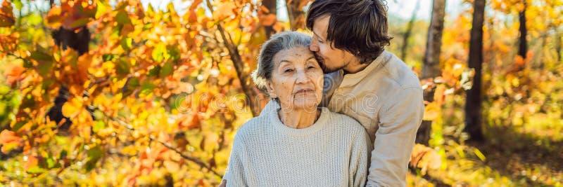 拥抱在秋天公园横幅,长的格式的祖母和成人孙子 库存图片