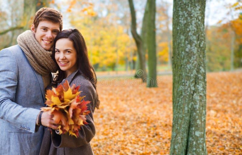 拥抱在秋天公园的微笑的夫妇 免版税库存图片