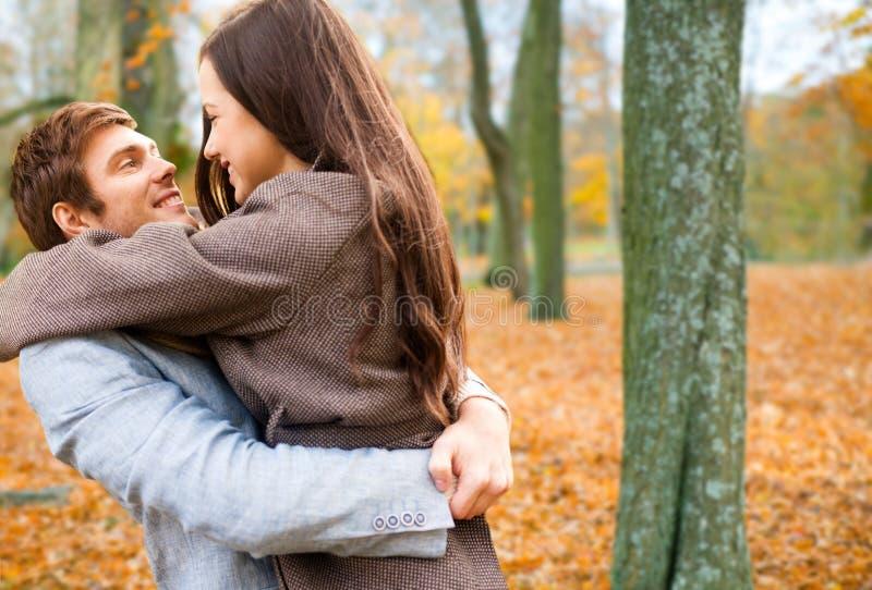 拥抱在秋天公园的微笑的夫妇 免版税库存照片