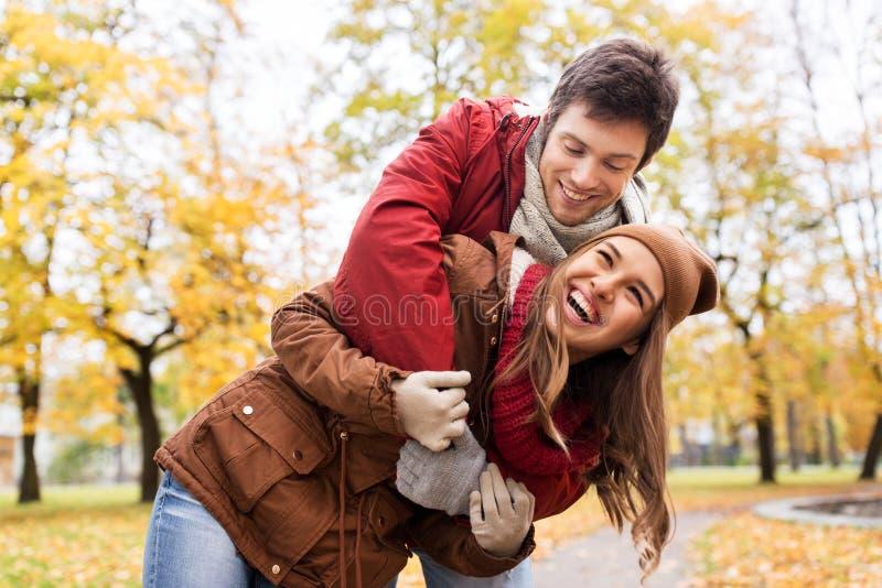 拥抱在秋天公园的愉快的年轻夫妇 库存图片