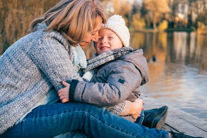 拥抱在秋天公园的母亲和孩子靠近湖 有获得的妈妈的愉快的儿子乐趣,放松,享有生活 母亲节,fami 图库摄影
