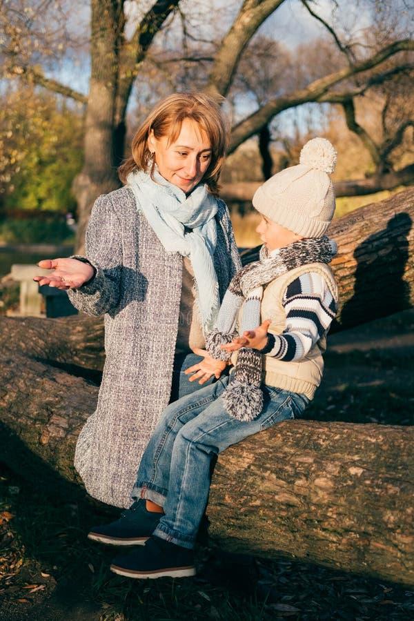 拥抱在秋天公园的母亲和孩子靠近湖 有获得的妈妈的愉快的儿子乐趣,放松,享有生活 免版税库存照片