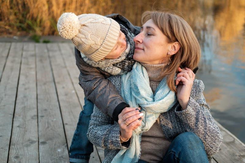 拥抱在秋天公园的母亲和孩子靠近湖 有获得的妈妈的愉快的儿子乐趣,放松,享有生活 库存图片