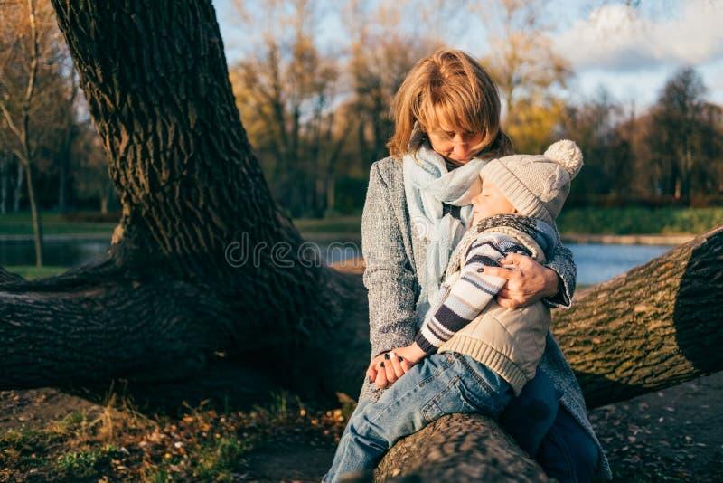 拥抱在秋天公园的母亲和孩子靠近湖 免版税库存照片