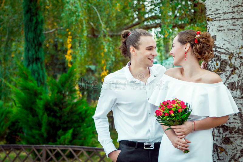 拥抱在秋天的愉快的爱恋的婚礼夫妇停放 免版税库存图片
