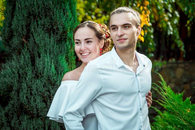 拥抱在秋天的愉快的爱恋的婚礼夫妇停放 免版税图库摄影