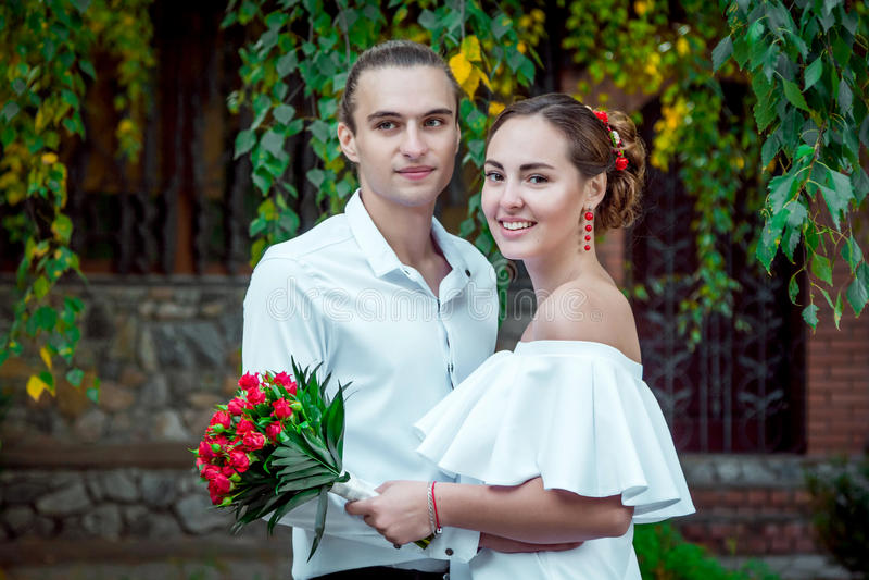 拥抱在秋天的愉快的爱恋的婚礼夫妇停放 库存照片