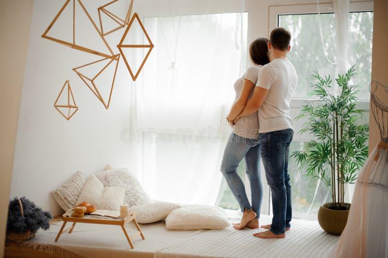 拥抱在窗口附近的年轻夫妇后面看法  库存图片