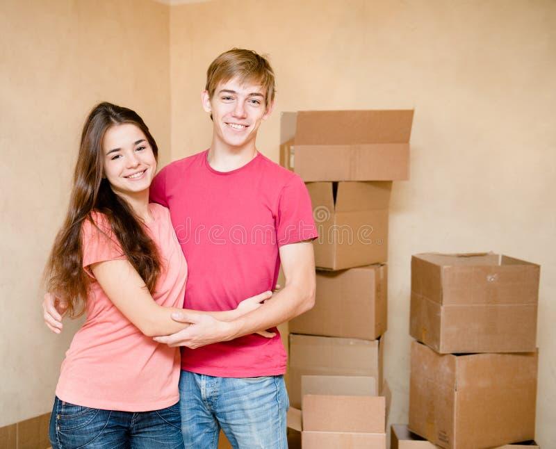 拥抱在纸板箱背景的愉快的年轻家庭  免版税图库摄影