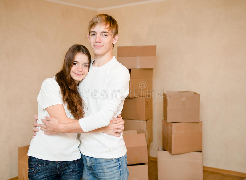 拥抱在纸板箱背景的逗人喜爱的年轻夫妇  库存照片