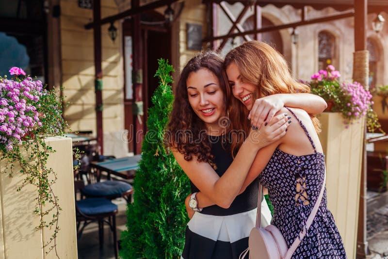 拥抱在老城市街道上的愉快的女性朋友在夏天 最佳的妇女朋友的真正的情感 免版税图库摄影