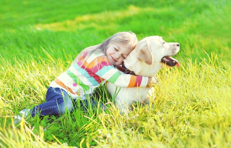 拥抱在草的愉快的孩子拉布拉多猎犬狗 免版税库存图片
