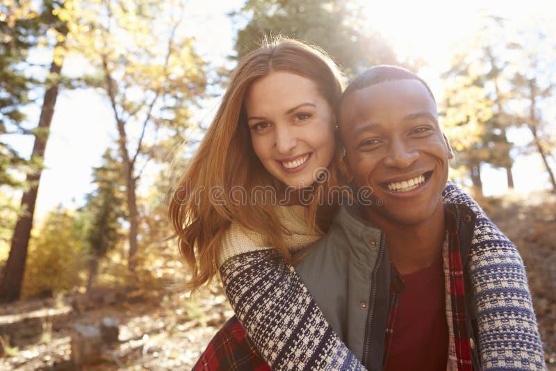 拥抱在远足期间的愉快的混合的族种夫妇在森林里 免版税库存图片