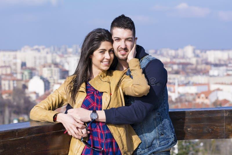 拥抱在都市风景背景的美好的夫妇 免版税库存照片