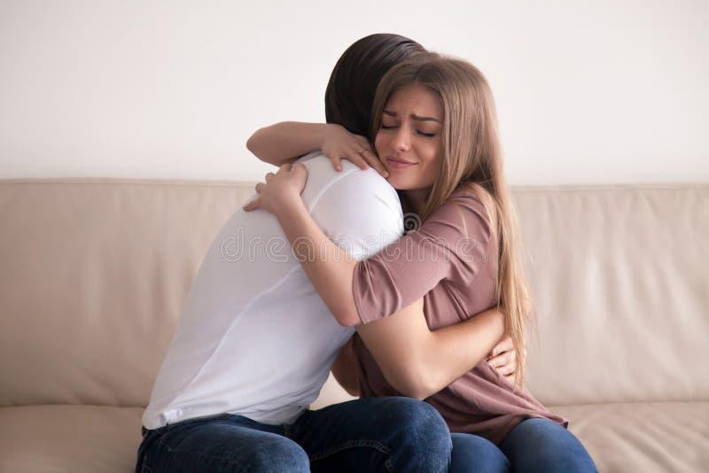 拥抱在长沙发的年轻夫妇画象紧的开会户内 免版税库存照片