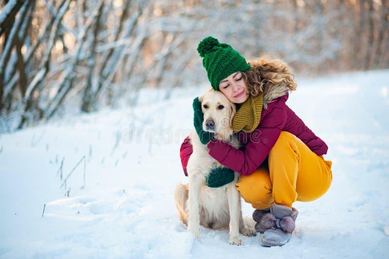 拥抱在雪的年轻美丽的妇女金毛猎犬狗 库存照片