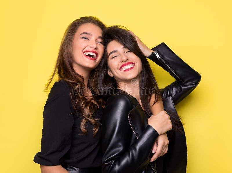 拥抱在黄色背景的两美女 免版税库存图片