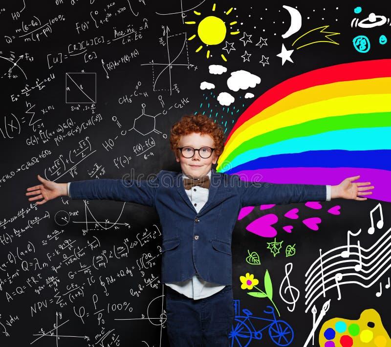 拥抱在黑板背景的愉快的小男孩宇宙与科学和艺术样式 库存图片