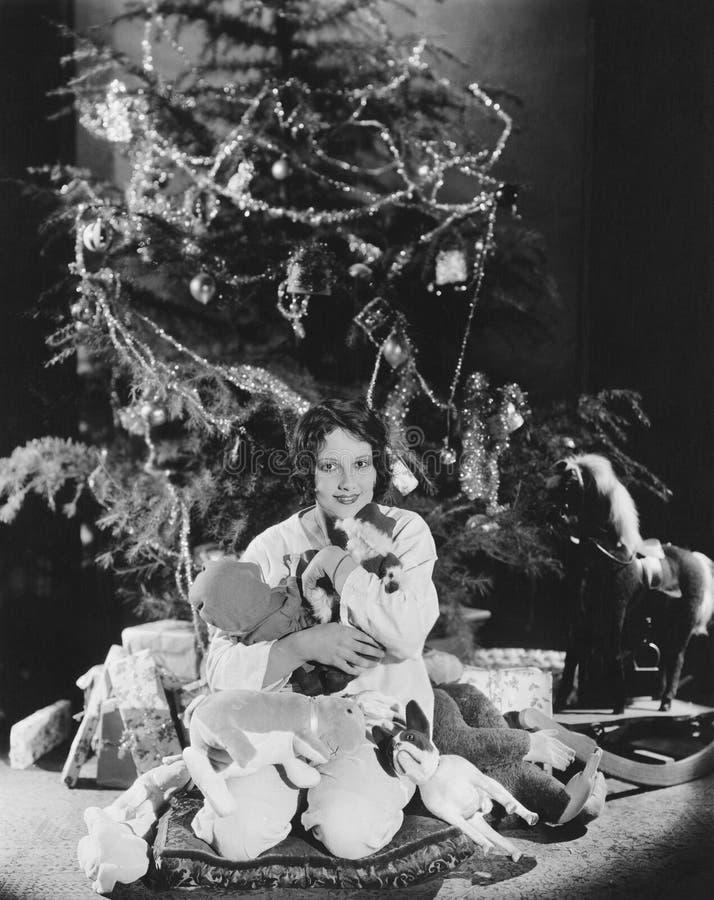拥抱填充动物玩偶的十几岁的女孩在圣诞树下(所有人被描述不更长生存,并且庄园不存在 suppl 免版税库存图片