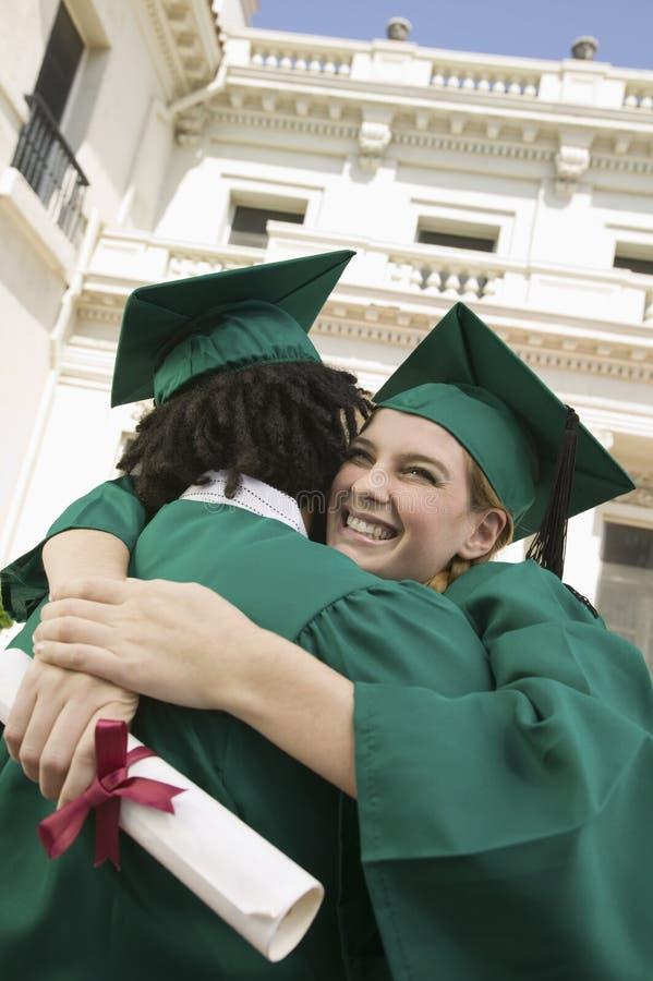 拥抱外部大学的两个毕业生 免版税图库摄影