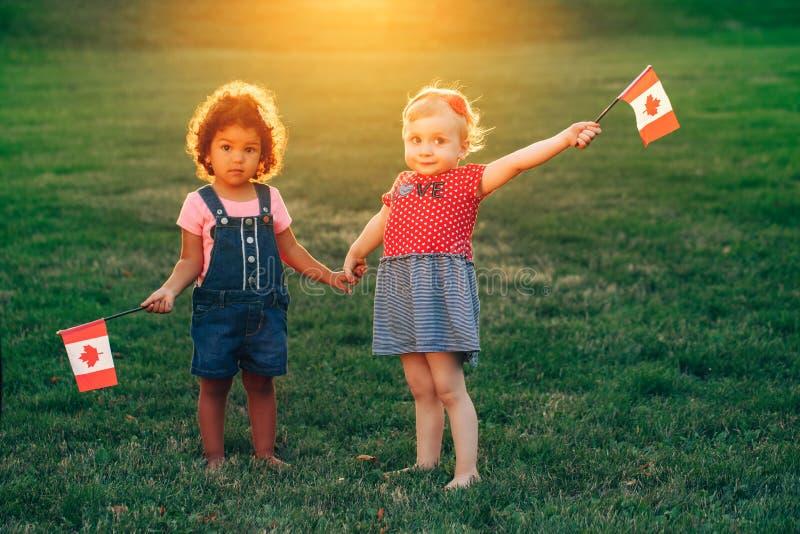 拥抱外面在公园的白白种人和拉丁西班牙婴孩 免版税库存照片
