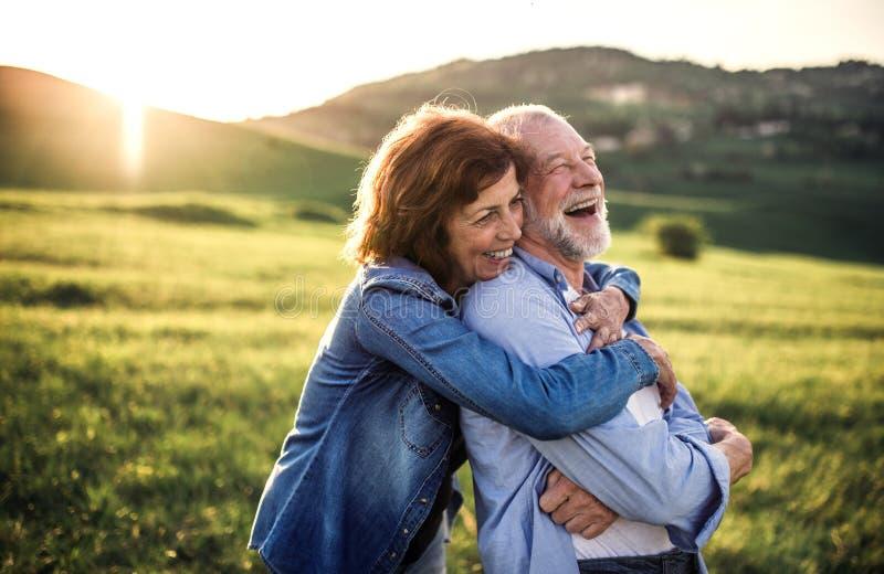 拥抱外面在春天自然的资深夫妇侧视图在日落 免版税库存照片
