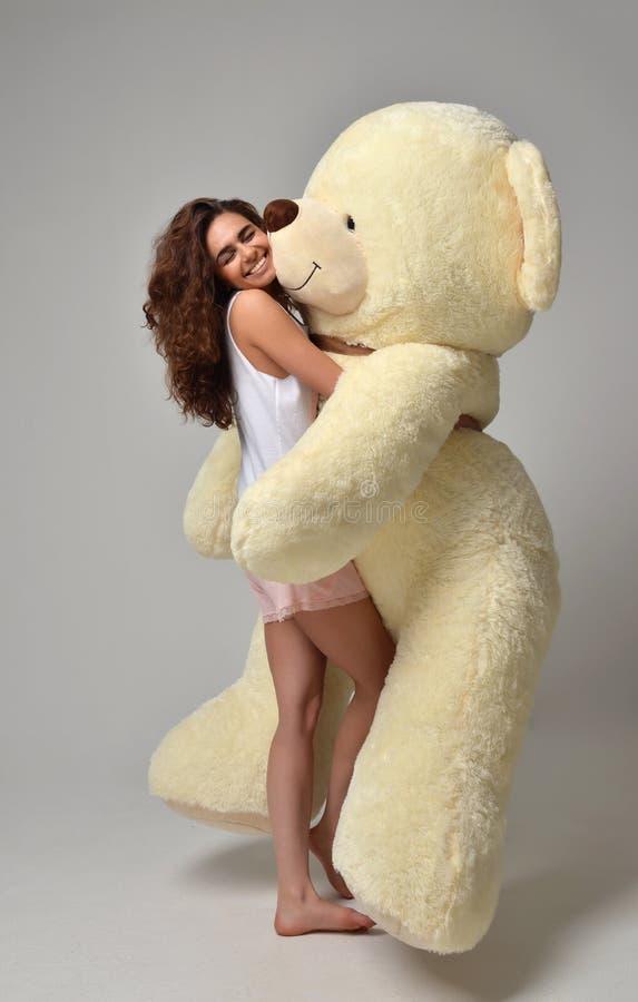 拥抱大玩具熊软的玩具愉快的smili的年轻美丽的女孩 免版税库存照片