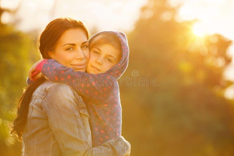 拥抱女儿的愉快的母亲 免版税图库摄影