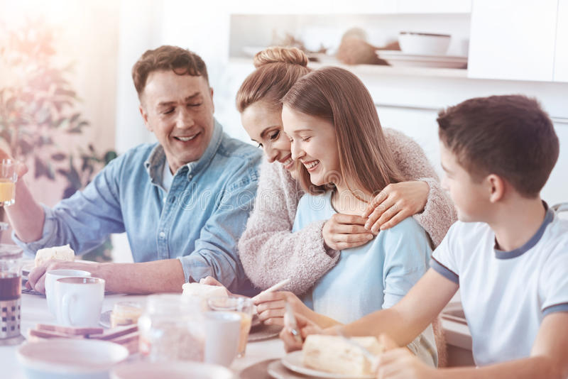拥抱女儿的感伤的母亲在家庭早餐期间 免版税库存照片