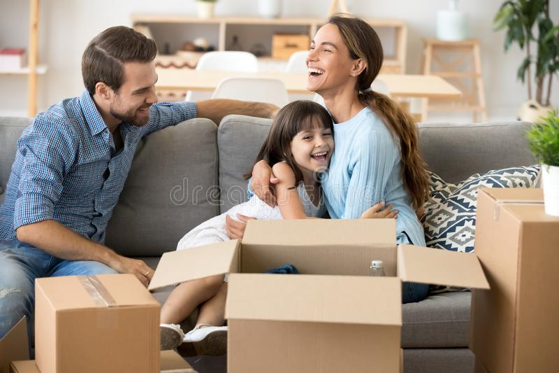 拥抱女儿,家庭的微笑的妈妈打开在新的舱内甲板的箱子 免版税图库摄影