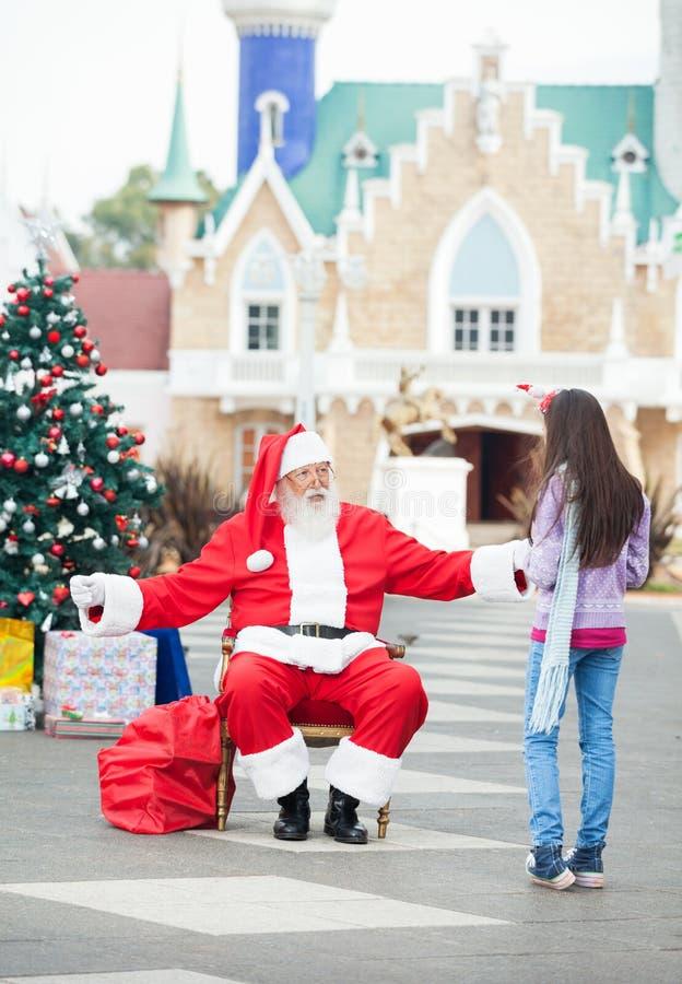 拥抱女孩的圣诞老人 库存照片