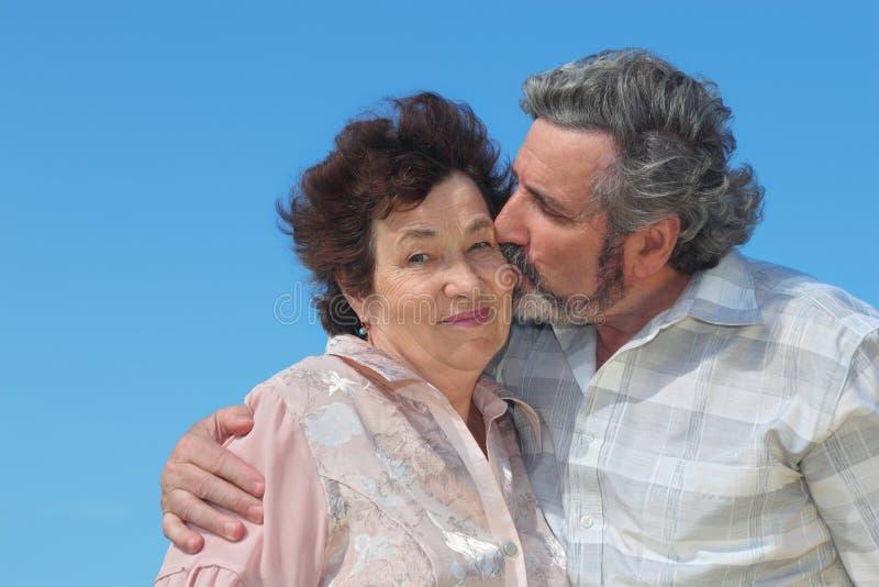 拥抱她亲吻的人老妇人的面颊 免版税库存照片