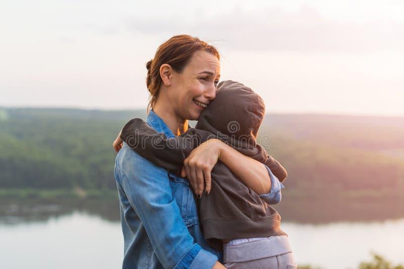 拥抱她儿子和哭泣的母亲 免版税图库摄影