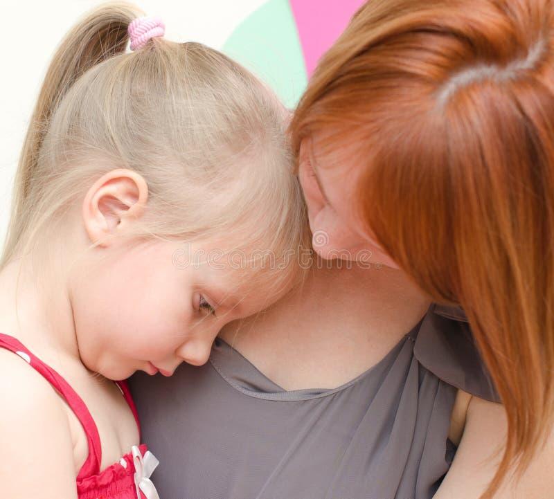 拥抱哀伤的孩子的母亲 免版税库存照片