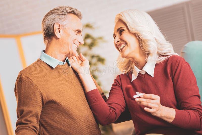 拥抱她爱恋的丈夫的微笑的愉快的妻子 免版税库存图片