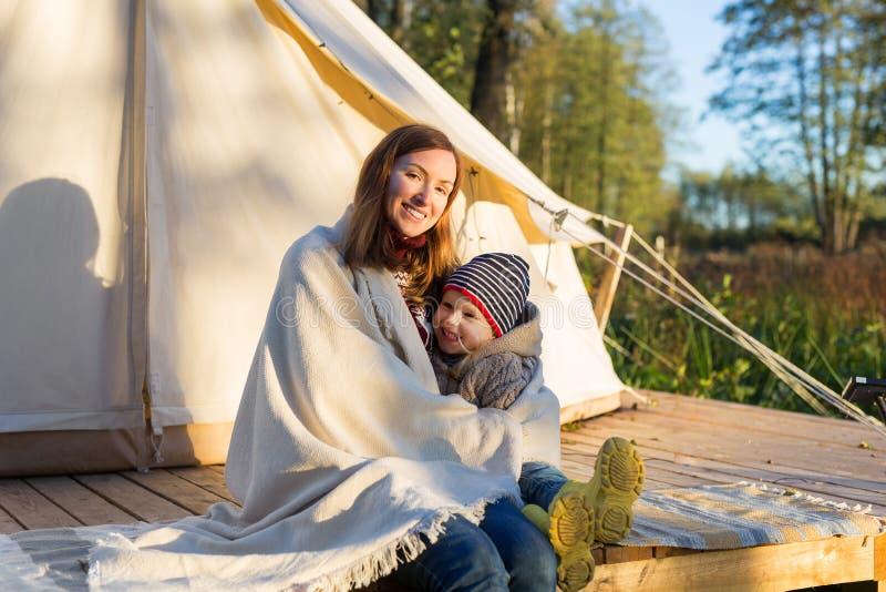 拥抱她的与毯子的年轻母亲孩子,当坐在帆布帐篷附近时 免版税库存照片