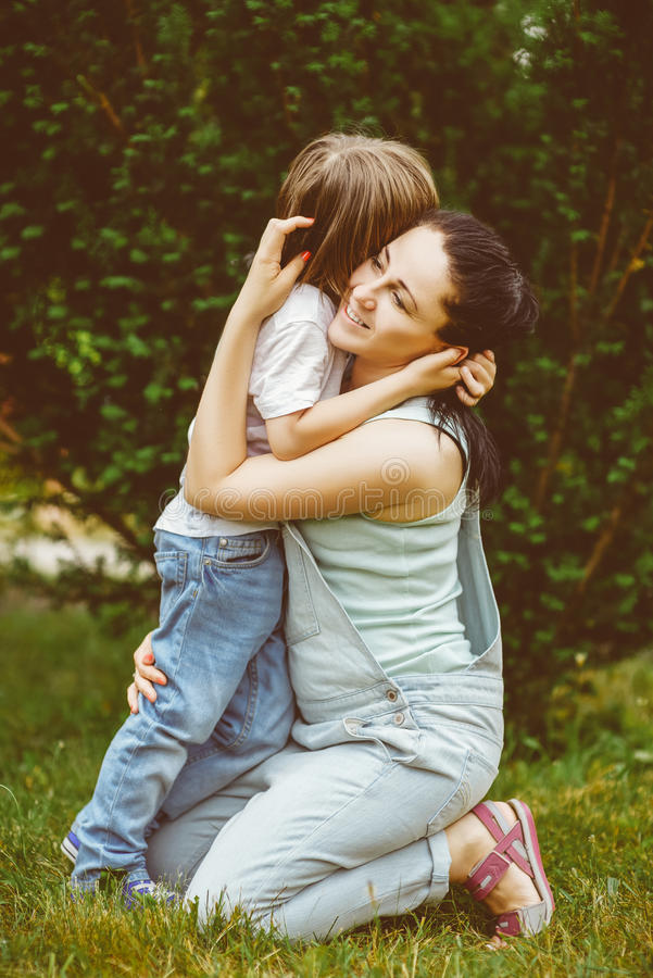 拥抱她的儿子的爱恋的母亲 免版税图库摄影
