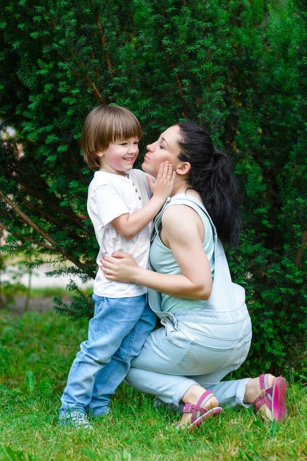 拥抱她的儿子的爱恋的母亲 免版税库存照片