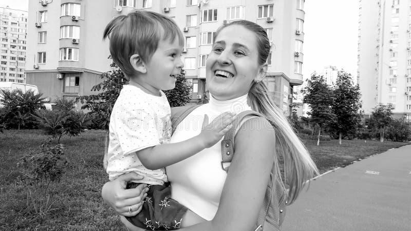 拥抱她的儿童儿子的愉快的微笑的年轻母亲黑白画象走在城市街道上 免版税库存照片