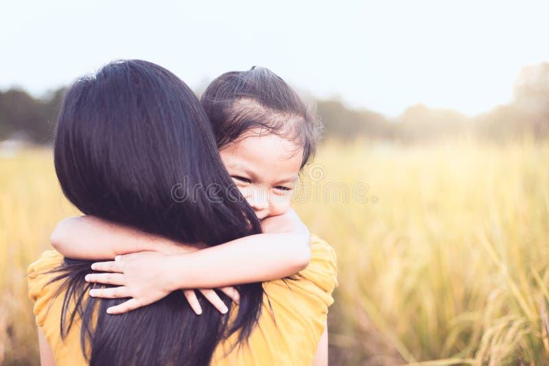 拥抱她的充满爱的愉快的亚裔小孩女孩母亲 图库摄影