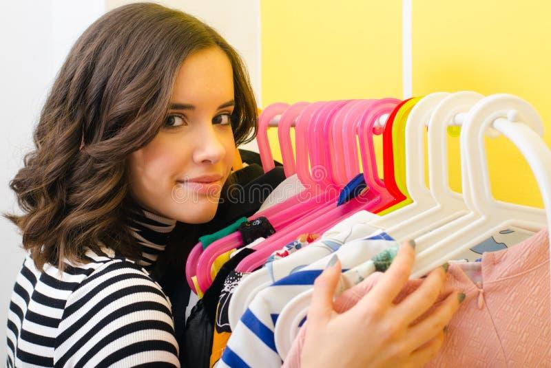 拥抱她的在挂衣架的愉快的微笑的女孩衣裳 免版税库存图片