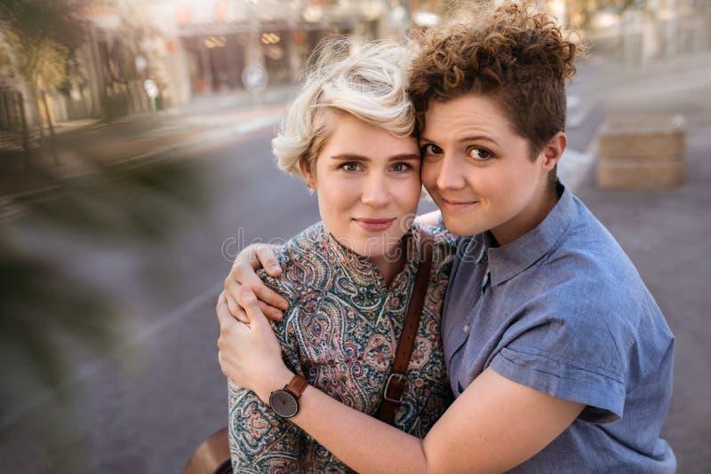 拥抱她的女朋友的微笑的年轻女人在城市 库存照片