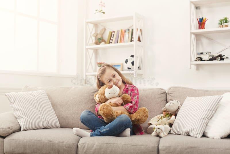 拥抱她的女用连杉衬裤的愉快的矮小的女孩在家涉及沙发 库存图片